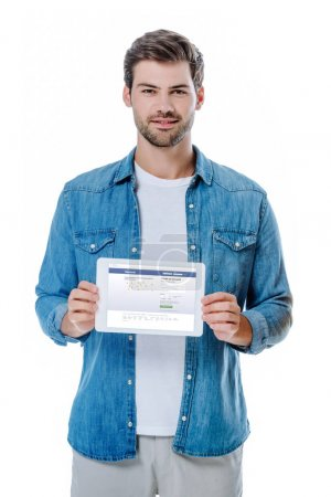 Photo for KYIV, UKRAINE - AUGUST 12, 2019: smiling man in denim shirt holding digital tablet with facebook page isolated on white - Royalty Free Image