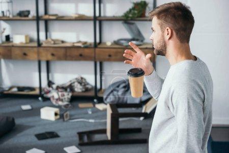 Photo pour Vue latérale de l'homme choqué tomber tasse en papier et en regardant l'appartement volé - image libre de droit