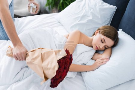 Photo for Cropped view of man holding gift, bouquet and woman sleeping in bed - Royalty Free Image