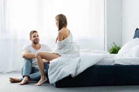 Photo pour Bel homme souriant parlant avec une femme dans l'appartement - image libre de droit