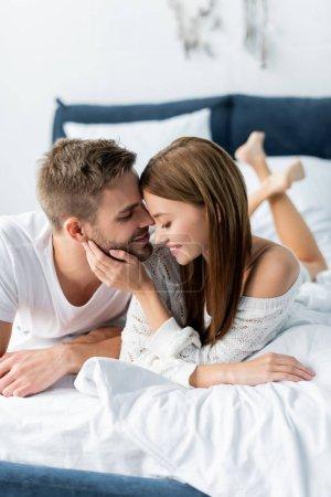 Photo pour Attrayant et souriant femme étreignant bel homme dans l'appartement - image libre de droit
