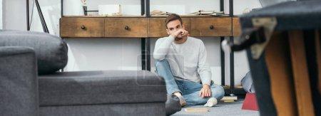 Photo pour Photo panoramique d'un bel homme assis dans un appartement volé - image libre de droit