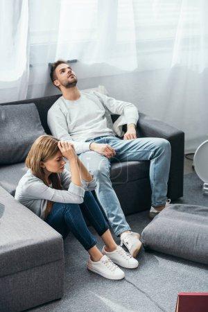 Photo pour Triste femme assise au sol et bel homme assis sur un canapé dans un appartement volé - image libre de droit