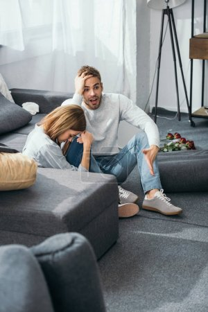 Photo for Sad woman and shocked man sitting on floor in robbed apartment - Royalty Free Image