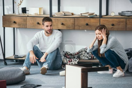 sad woman and handsome man sitting on floor in robbed apartment