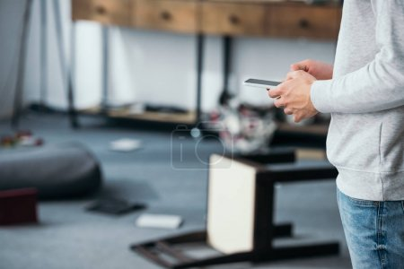 Photo for Cropped view of man using smartphone in robbed apartment - Royalty Free Image