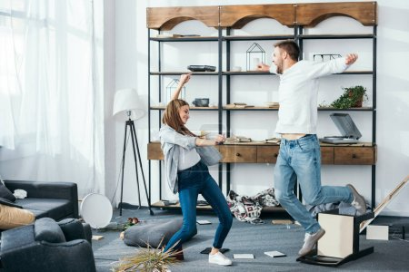 Photo for Smiling woman and handsome man with outstretched hands dancing in robbed apartment - Royalty Free Image