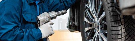 Photo pour Vue en coupe de la clé pneumatique près de la roue de la voiture, prise de vue panoramique - image libre de droit