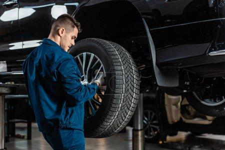 Photo pour Jeune mécanicien installant la roue sur la voiture surélevée dans l'atelier - image libre de droit