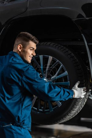 smiling mechanic installing wheel on raised car in workshop