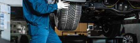 Photo for Cropped view of mechanic installing wheel on car in workshop, panoramic shot - Royalty Free Image