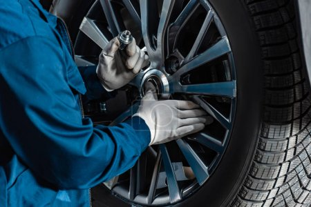 cropped view of mechanic fixing wheel on car in workshop