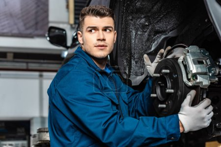Photo for Serious mechanic adjusting disc brakes and looking away - Royalty Free Image
