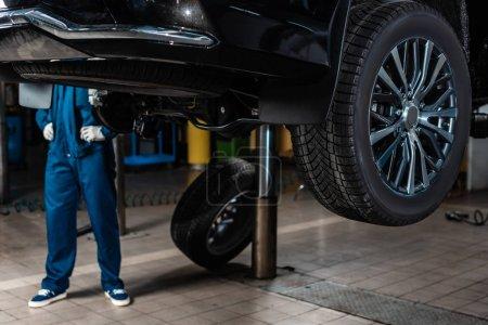 Photo pour Vue recadrée du mécanicien debout près du wagon soulevé sur le monte-charge - image libre de droit