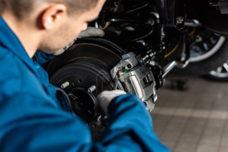 Photo for Selective focus of mechanic adjusting brake caliper with screw driver - Royalty Free Image