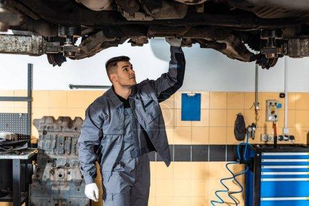 Photo pour Un mécanicien attentif examine une voiture surélevée en atelier - image libre de droit