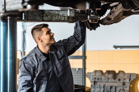 Photo for Young mechanic inspecting raised car in workshop - Royalty Free Image