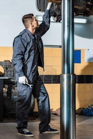 Photo pour Jeune mécanicien inspectant une voiture surélevée en atelier - image libre de droit