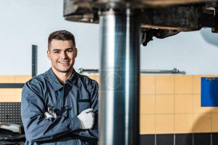 Photo pour Un mécanicien souriant regardant une caméra près d'une voiture surélevée dans un atelier - image libre de droit
