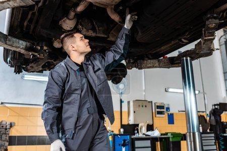 Photo pour Inspection mécanique attentive du fond d'une voiture surélevée en atelier - image libre de droit
