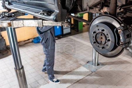 Photo pour Mise au point sélective des freins à disque assemblés près d'un jeune mécanicien examinant une voiture surélevée - image libre de droit