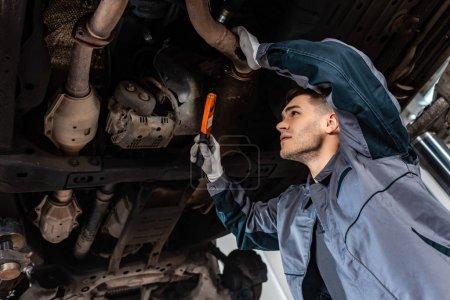 Photo pour Mécanicien attentif inspectant le fond de la voiture avec lampe de poche - image libre de droit