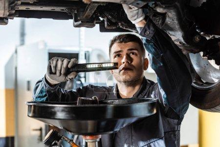 Photo pour Un mécanicien attentif inspectant le fond de la voiture avec une lampe de poche près de l'extracteur d'huile usée - image libre de droit