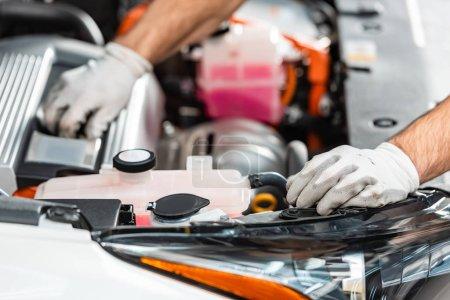 Photo pour Vue recadrée du mécanicien inspectant le compartiment moteur de la voiture - image libre de droit