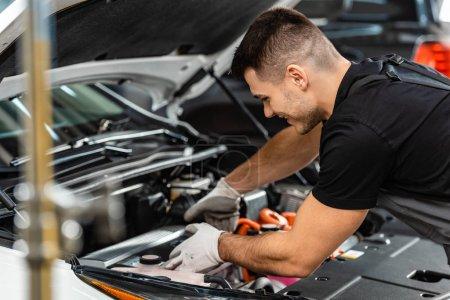 Photo pour Foyer sélectif du mécanicien souriant inspectant le compartiment moteur de voiture - image libre de droit