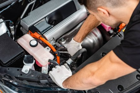 Photo pour Vue aérienne du jeune mécanicien inspectant le compartiment moteur de la voiture - image libre de droit