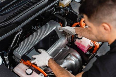 vue aérienne du jeune mécanicien inspectant le compartiment moteur de la voiture