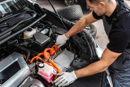 Photo pour Jeune mécanicien inspectant le compartiment moteur de la voiture - image libre de droit