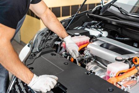 Photo pour Vue partielle du mécanicien inspectant le compartiment moteur de la voiture - image libre de droit