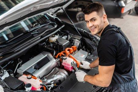 Photo pour Beau mécanicien inspectant compartiment moteur de voiture et souriant à la caméra - image libre de droit
