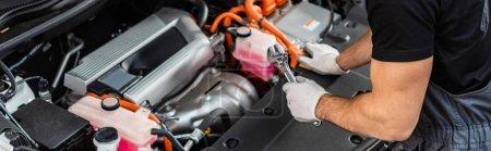 Photo pour Vue partielle du mécanicien inspectant le compartiment moteur de la voiture, vue panoramique - image libre de droit
