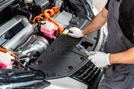 Photo for Partial view of mechanic holding wrench while inspecting car engine compartment - Royalty Free Image
