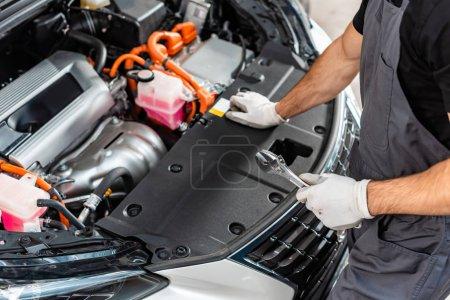 Photo pour Vue partielle de la clé de maintien du mécanicien lors de l'inspection du compartiment moteur de la voiture - image libre de droit