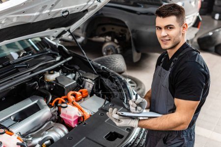 Photo for Handsome mechanic writing on clipboard while inspecting car engine compartment - Royalty Free Image
