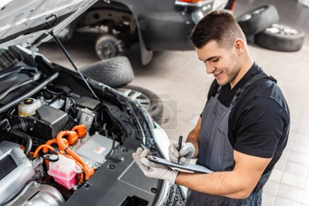 Photo for Smiling mechanic writing on clipboard while inspecting car engine compartment - Royalty Free Image