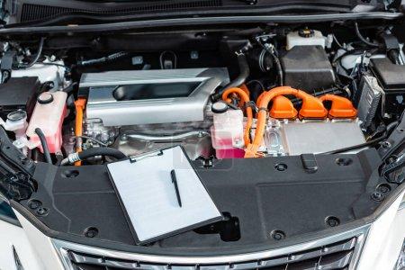 Photo pour Presse-papiers avec papier blanc vierge et stylo près du compartiment moteur de la voiture - image libre de droit