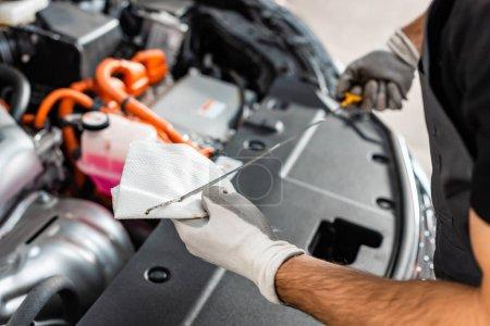 Photo pour Vue recadrée du mécanicien essuyant la jauge d'huile avec chiffon près du compartiment moteur de la voiture - image libre de droit