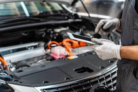 Photo pour Vue partielle du mécanicien utilisant une tablette numérique près du compartiment moteur de la voiture - image libre de droit