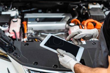 Foto de Vista cromada de mecánica mediante tableta digital cerca del compartimiento del motor del automóvil. - Imagen libre de derechos