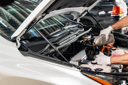 Photo pour Vue partielle du mécanicien versant l'huile moteur au moteur de voiture - image libre de droit