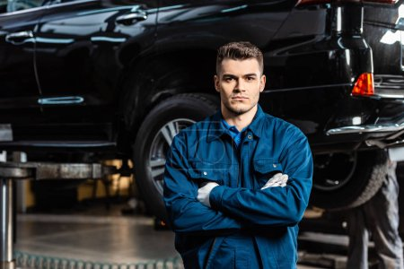 Photo for Handsome, serious mechanic standing with crossed arms and looking at camera - Royalty Free Image