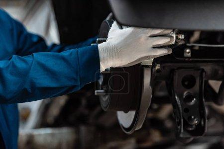 Photo pour Vue recadrée du mécanicien installant la plaquette de frein sur les freins à disque - image libre de droit