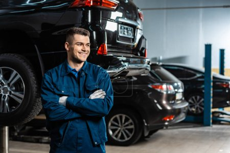 Photo for Young, smiling mechanic standing with crossed arms and looking away near modern cars in workshop - Royalty Free Image