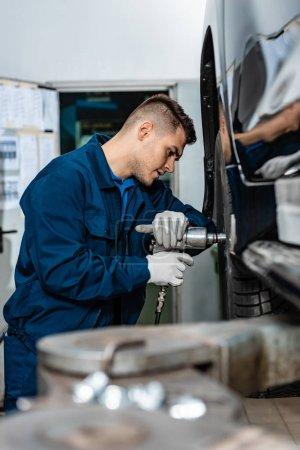 Photo pour Focalisation sélective des jeunes mécaniciens installant la roue sur la voiture en atelier - image libre de droit