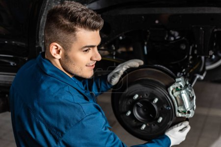 Photo for Handsome mechanic adjusting assembled disc brakes with brake caliper - Royalty Free Image