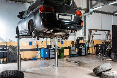 Photo for Modern black car raised on car lift in workshop - Royalty Free Image